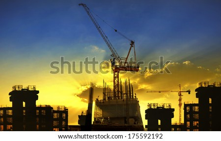 building and crane construction site against beautiful dramatic in dusky sky