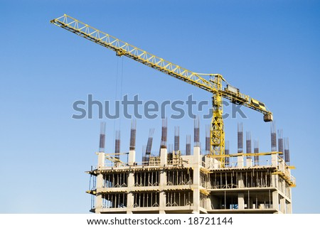 building and crane on clear blue sky
