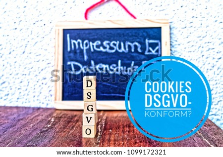 Building blocks with the inscription DSGVO (Datenschutzgrundverordnung) in English GDPR and a board with   Imprint and Privacy Policy and Cookies DSGVO-compliant (in german Cookies DSGVO-konform) #1099172321