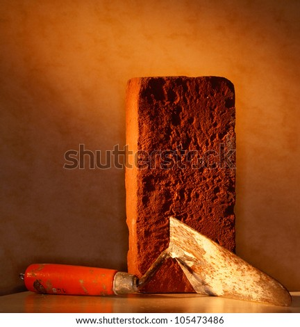 Building brick and bricklayers trowel. Studio shot as iconic still life in warm directional light