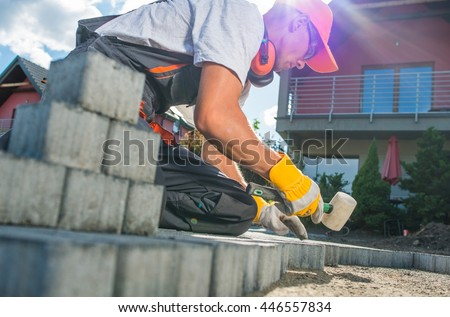 Building Brick Garden Path. Caucasian Worker Building Block Paved Hardstanding Garden Path. Brick Paving.