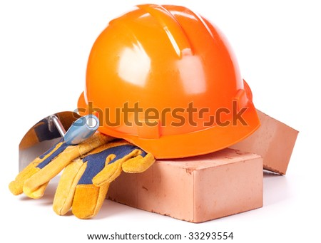 Building bricks, hard hat, trowel and gloves on a white background