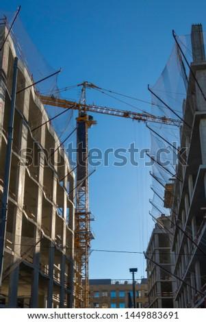 Building complex construction site. Yellow crane against blue sky.   #1449883691