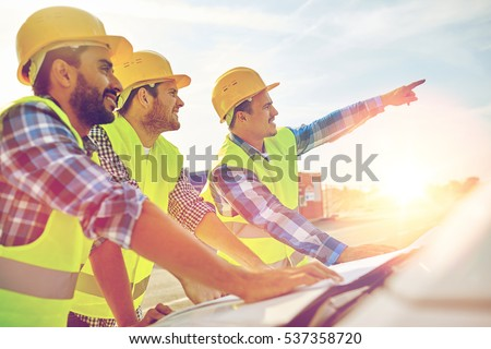 building, construction, development, teamwork and people concept - close up of builders in hardhats and high visible vests with blueprint on car hood