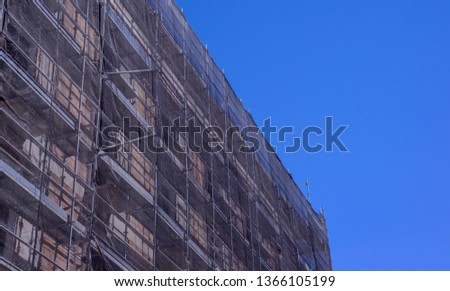 Building construction site covered in gray transparent tarpaul. 