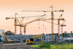 building construction site with tower crane and backhoe machinery in sunset vintage tone color
