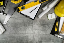 Building contractor background. Yellow tools on gray tiles.