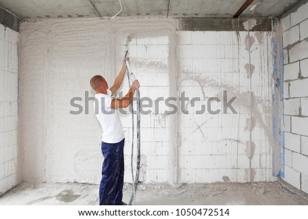 Building contractor plastering walls with a plastering pump machine indoor.