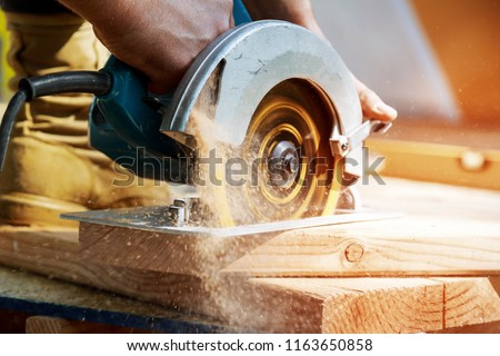 Building contractor worker using hand held worm drive circular saw to cut boards on a new home constructiion project