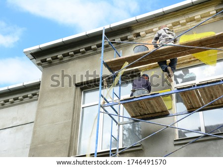 Building contractors on scaffolding near rooftop are rendering, plastering, stucco coating the exterior wall of the building using fiberglass plaster mesh for facade and decoration works. Photo stock ©