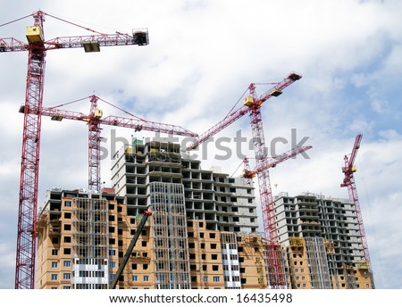 Building crane and building under construction against cloudy sky