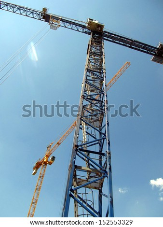 Building cranes on a background of clear sky