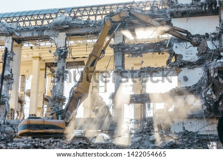 Building demolition excavator with long mechanical arm. Destruction of a house, reconstruction, bricks and metal, ruins, concrete dust in the air. Heavy machinery, hydraulic construction equipment.