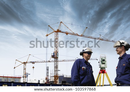 building engineers with total-station instrument and construction site