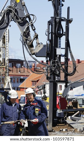 building engineers with total-station instrument and construction site - stock photo