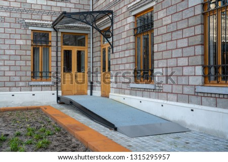 Building entrance with barrier free access ramp for disabled person wheelchair  Stock foto ©