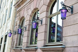 Building facade. Old building exterior with windows and lanterns. Historic building structure. Architectural structure. Urban architecture and construction. City building. Town house.