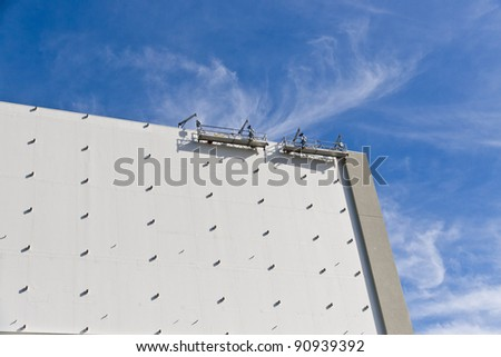 Building facade or billboard construction against blue sky