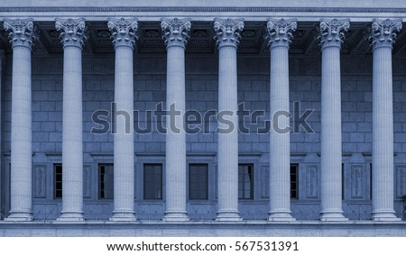 Building facade with corinthian columns in a colonnade. Neoclassical style, resembling a law court / courthouse, university, library or public administration building. Blue color tone.
