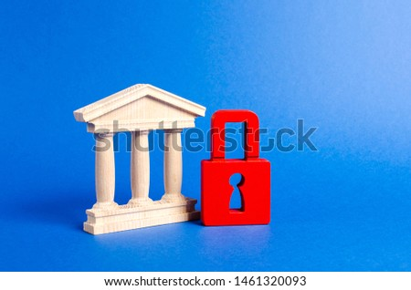 Building figurine with pillars in antique style and red padlock. Ineffective government, seizure of property and liquidation of the bank. Saving architectural heritage and historical monuments. #1461320093