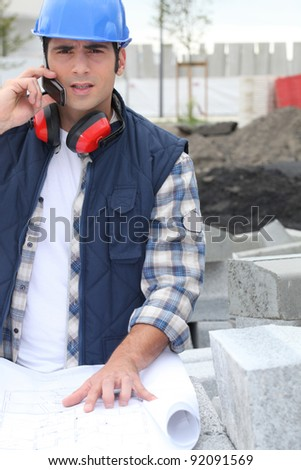 Building foreman with a phone and plans