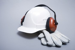 Building helmet, ear-phones and protective gloves on a grey background