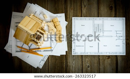 Building house. House construction. Many drawings for building and wooden house on old wooden background.