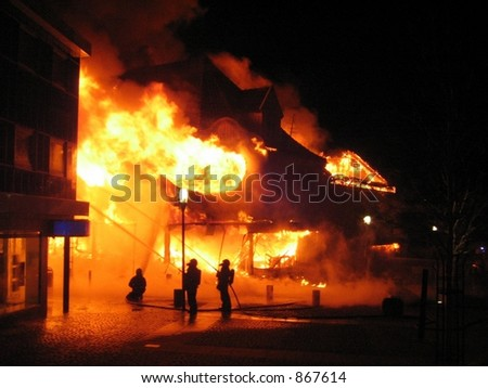 Building in a fire inferno, and some firefighters desperately trying to get control of the flames (some noise)