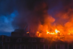 Building in fire, burning fire flame with smoke on the apartment house roof at night in the city.