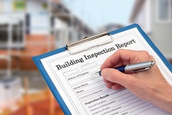 Building Inspector completing an inspection form on clipboard