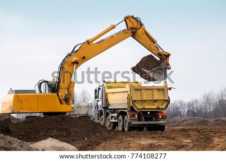 Building Machines: Digger loading trucks with soil