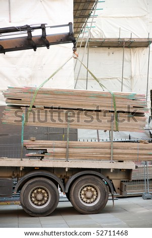 Building material loaded onto the trailer of a truck  at a building site