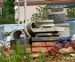 Building materials are stored behind a mesh fence. Concrete rings and blocks are stacked. The filled sacks are piled up. Background with building materials.