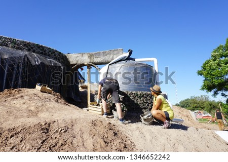 Building materials, frames and structures of a Earthship Sustainable house construction. Walls Made with bottles and other recycled material like tires and cans used as bricks.
