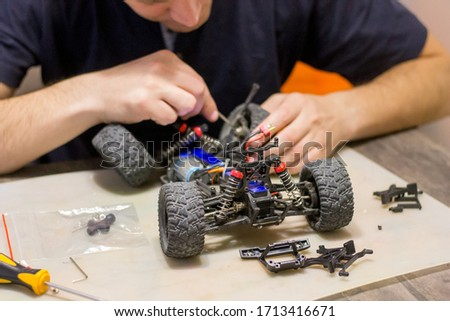 Building model cars. Radio control car assembly scene, RC car assembly on wooden work desk and tools. Building model cars. Radio control car assembly scene, RC car assembly on work desk and tools.