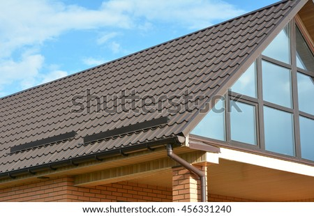 Building Modern House Construction with metal roof, rain gutter system and roof protection from snow board, snow bar (Snow guard). Roof Snow Guards: Building Materials & Supplies