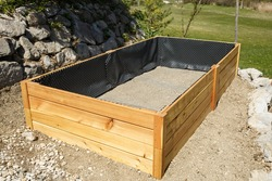 Building new wooden frame for a raised garden bed. DIY concept. Sustainable living