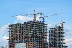 Building of high-rise construction, working cranes on background