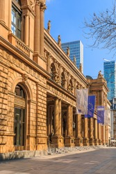 Building of the stock exchange in Frankfurt with flags above entrance. brown colored historical commercial building in baroque style. Skyscrapers in the background. Trees in the foreground in spring