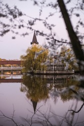 Building on a lake . Bridge, chapel and building with trees on a lake and unfocused bloomihg white tree on first ground.