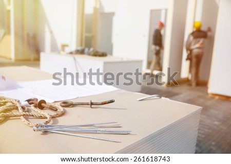 Building plan, eye bolt and screws on plasterboard panels with workers in background