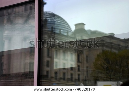 building reflections in a window in berlin, the parliament of Germany reflected in a glass front #748328179