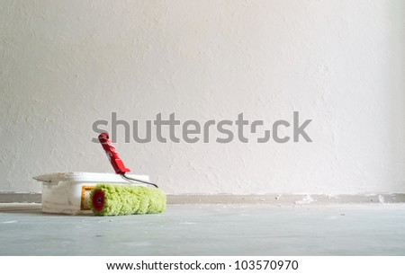 Building roller in an empty room where wall covered with a white decorative plaster - stock photo