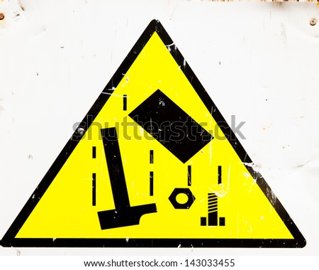 building site danger sign for falling objects with signs of impact on it
