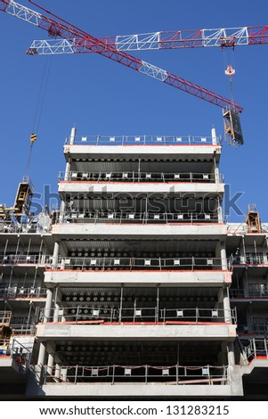 building site with two cranes in blue sky