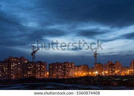 building site with two tower cranes against the background of multi-storey houses and a dark blue sky, night scene