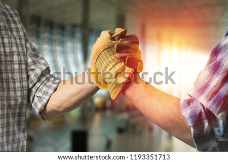 building, teamwork, partnership, gesture and people concept - close up of builders hands in gloves greeting each other with handshake on construction site #1193351713