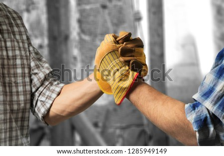 building, teamwork, partnership, gesture and people concept - close up of builders hands in gloves greeting each other with handshake on construction site #1285949149
