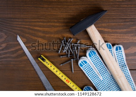 Building tools. Hammer, nails, hacksaw, tape measure and gloves on a wooden background
