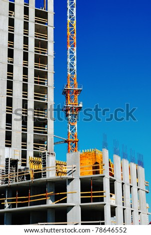 Building under construction with crane on blue sky. Industrial image